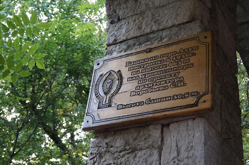 Деревянная вывеска у входа в башню - фото