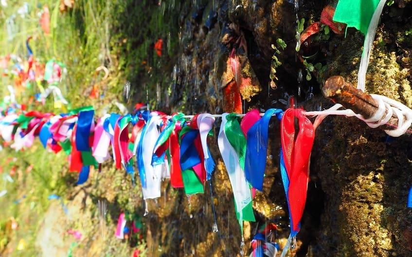 Яркие ленточки украшающие скалы - фото